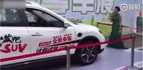 Une femme se met devant une voiture pour tester le freinage automatique d'une voiture