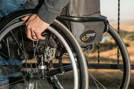 La jeune femme est bloquée par l'homme en fauteuil roulant – elle fait quelque chose qu'il n'est pas évident de faire