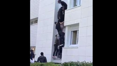 Des jeunes forment une échelle humaine contre un immeuble pour sauver un couple et son bébé desflammes