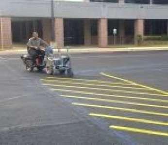 Un homme gère un traceur de lignes sur un parking (Texas)