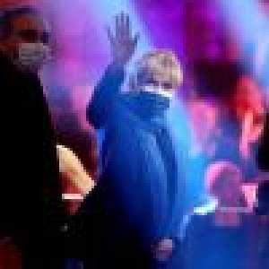 Brigitte Macron stylée en blazer bleu, elle écoute la